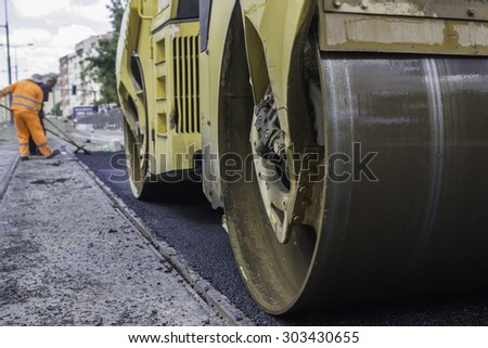 Road roller compacting with defocused construction workers in background - stock photo