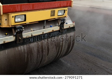 road roller flattening new asphalt - stock photo