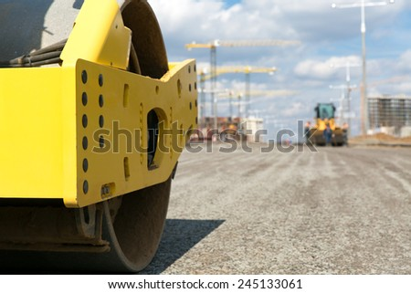 Road roller vibration machine compacting gravel base for asphalt pavement during construction roadworks - stock photo
