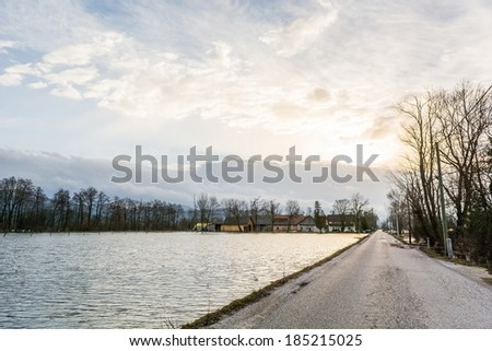 Road running along flooded field  after spring thaw