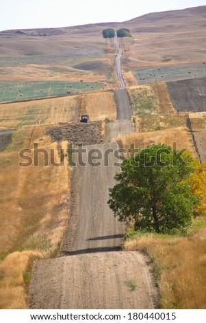 Road running Saskatchewan's rolling hills - stock photo
