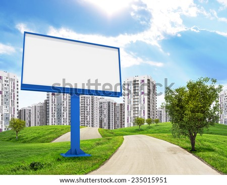 Road running through green hills with a few trees, leading toward city, Blank billboard and tree on foreground. High-rise buildings as backdrop. - stock photo