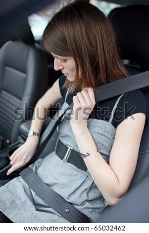 Road safety concept - Pretty young woman fastening her seat belt in a car - stock photo