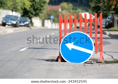 Road sign and barrier at city street due a pothole - stock photo