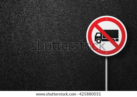Road sign circular shape with a picture of the truck. Behind the signs one can see a smooth asphalt road. The texture of the tarmac, top view. - stock photo