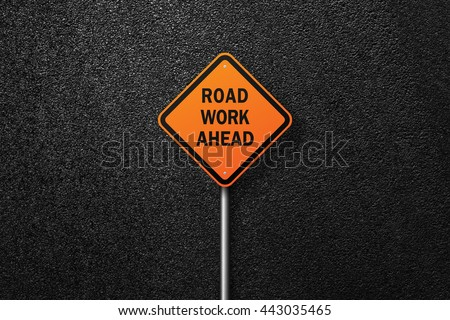 Road sign diamond shape. Behind the signs one can see a smooth asphalt road. ROAD WORK AHEAD. The texture of the tarmac, top view. - stock photo