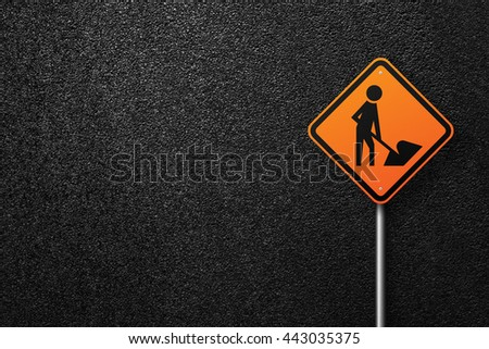 Road sign diamond shape with a picture of a worker. Behind the signs one can see a smooth asphalt road. Road works. The texture of the tarmac, top view. - stock photo