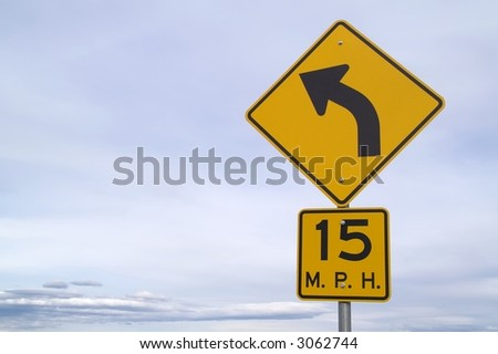Road sign for 15 mph curve positioned to right side of photo