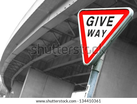 Road sign Give Way. British road sign Give Way opposite the motorway bridge by rainy day - stock photo