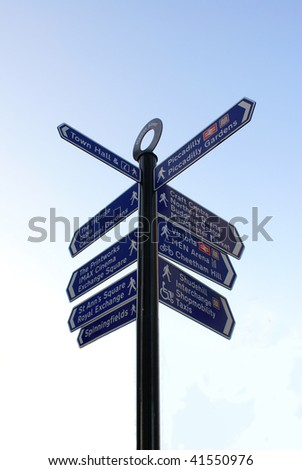 Road sign in different directions against a blue sky in Manchester . - stock photo