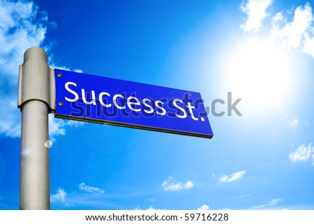 Road sign in front of a blue summer sky showing the way to Success Street - stock photo
