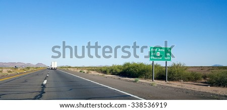 Road sign in the desert on Eastbound Interstate-10 showing 100 mile distance to the capital city of Phoenix, Arizona. - stock photo