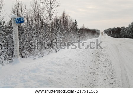 Road sign kilometer post in northern snowing road. Russia. Winter - stock photo