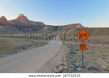 Road sign marking a dip with bullet holes in the Utah desert, USA. - stock photo
