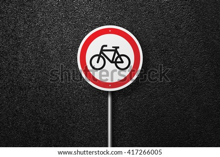 Road sign of the circular shape with a picture of the bike. Bike path. Behind the sign one can see a smooth asphalt road. The texture of the tarmac, top view. - stock photo