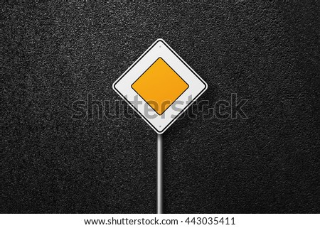 Road sign of the diamond shape. Behind the sign one can see a smooth asphalt road. Main road. The texture of the tarmac, top view. - stock photo