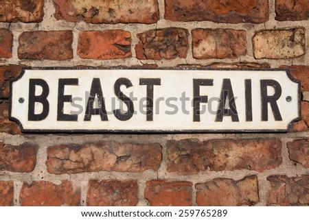 "Road Sign on a brick wall reading ""Beast Fair."" - stock photo"