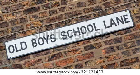 """Road Sign on a brick wall reading """"Old Boys School Lane."""" - stock photo"""