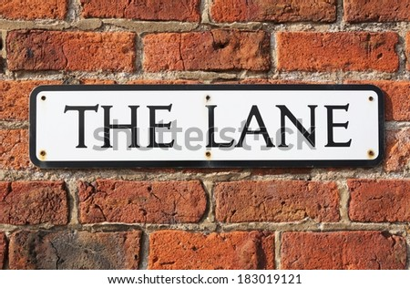 """Road Sign on a brick wall reading  """"The Lane."""" - stock photo"""