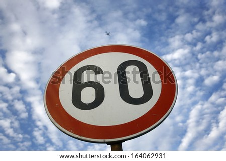 road sign speed limit sixty under cloudy blue sky - stock photo