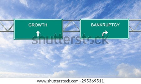 Road sign to bankruptcy and growth - stock photo