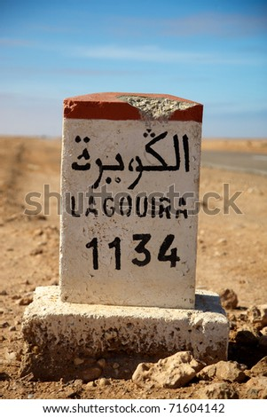 Road Sign to Lagouira in Morocco with blue sky - stock photo