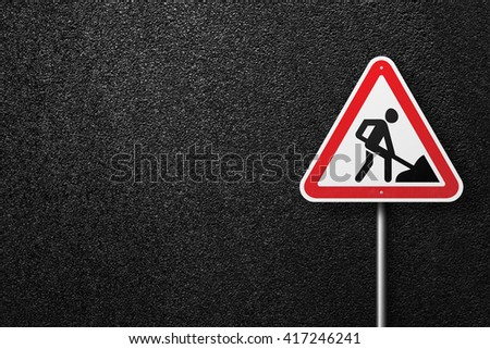 Road sign triangular shape with a picture of a worker. Behind the signs one can see a smooth asphalt road. Road works. The texture of the tarmac, top view. - stock photo
