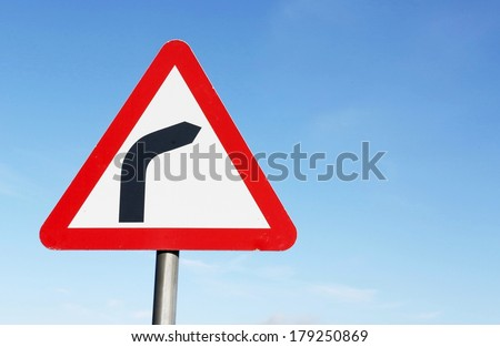 Road sign warning of a sharp bend ahead. - stock photo
