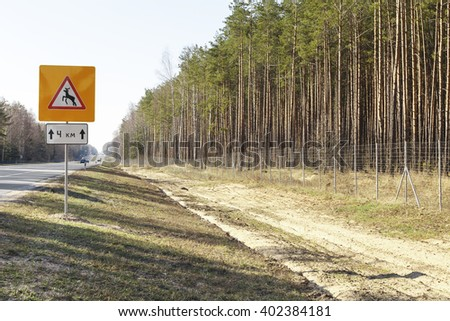 Road sign warning of wild animals and  fence fencing - stock photo