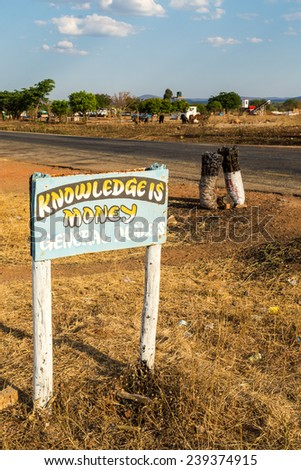 Road sign with charcoal bags along the road in africa, Tanzania - stock photo