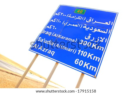 Road sign with direction to Iraq on desert road in Jordan - stock photo