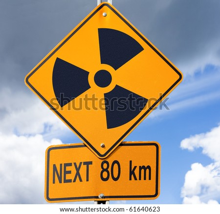Road sign with radioactivity warning symbol on it with dramatic sky background. - stock photo