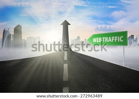 Road sign with Web Traffic word, pointing at a road turning into arrow upward symbolizing growing web activity - stock photo