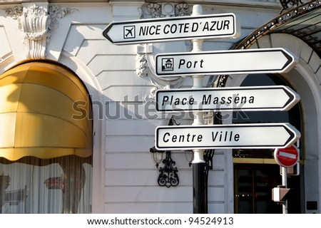 road signpost in nice france against fancy hotel facade - stock photo