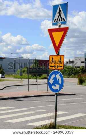 road signs at intersection roundabout, give way - stock photo