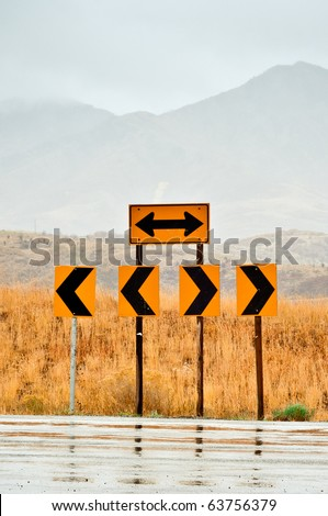 Road signs at the end of the road pointing left and right - stock photo