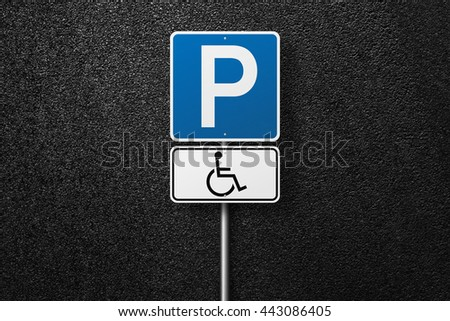 Road signs. Behind the signs one can see a smooth asphalt road. Disabled parking. The texture of the tarmac, top view. - stock photo