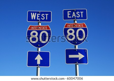 road signs for interstate 80 east and west with blue sky background