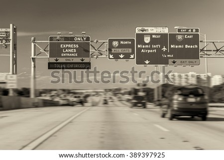 Road signs in Miami from a moving vehicle blurred. - stock photo