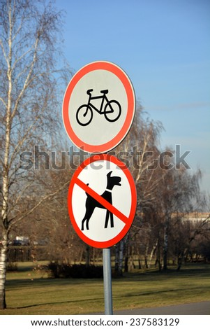 Road signs in park: No cycling and No dogs allowed - stock photo