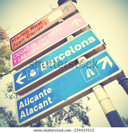 Road signs point ways to Barcelona and Alicante.  Instagram style filtred image - stock photo