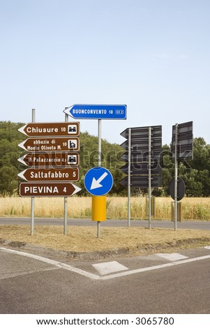 Road signs pointing different directions, Tuscany.