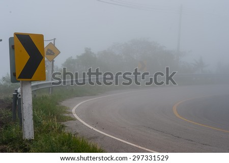 Road Signs warn Drivers for Ahead Dangerous Curve with fog. - stock photo