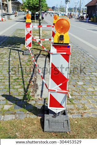 Road signs with flashers informing about some danger during pavement repair, Switzerland.