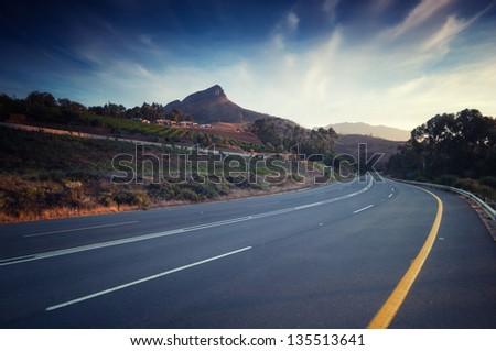Road sneaks through vineyar at sunset in stellenbosch - stock photo