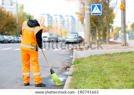 Road sweeper worker cleaning city street with broom tool  - stock photo