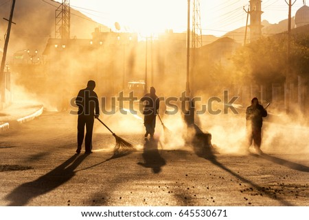 Road sweeper worker cleaning leh city market street with broom tool in early morning