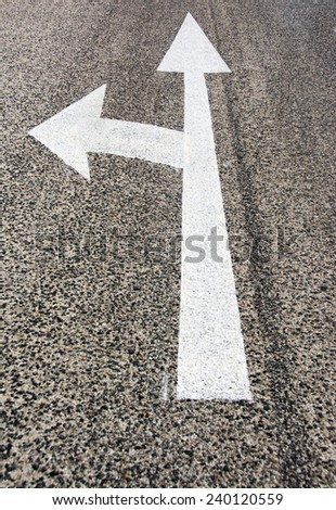 Road texture, white painted sign, left turn on way with poor quality asphalt.