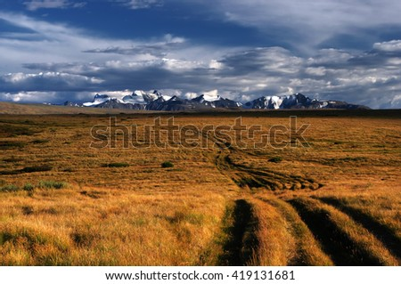 Road through a field of orange grass on highland steppe on a background of snow covered high mountains and glaciers under clouds and blue sky, Plateau Ukok, Altai mountains, Siberia, Russia - stock photo