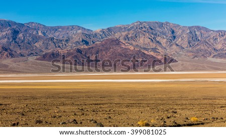 Road through canyons with lots of different topography. The road offers majestic views. It contains colorful rock formation. BADWATER RD, Death Valley National Park - stock photo